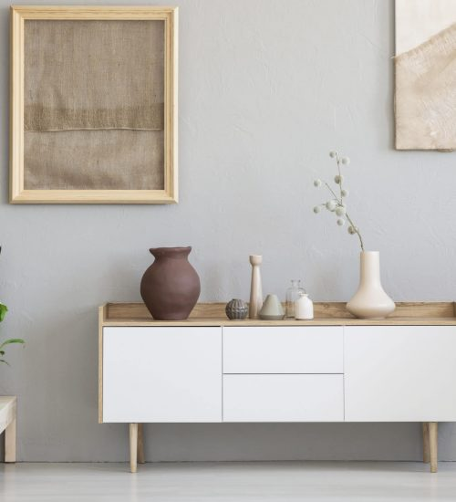Real photo of a botanic living room interior with burlap artwork on the gray wall and white cupboard surrounded by plants